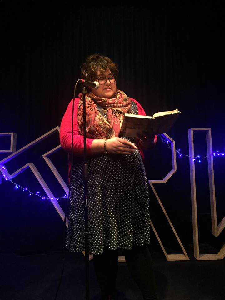 "Cynthia, a mid-fat light brown person with curly brown hair and black-rim glasses, stands on a stage behind a microphone stand holding an open notebook in her hands. She wears a green polka dot dress, a red and gold flowery scarf, a bracelet and a red cardigan. Some blue fairy lights and the letters ""FTRW"" can be seen on the background."