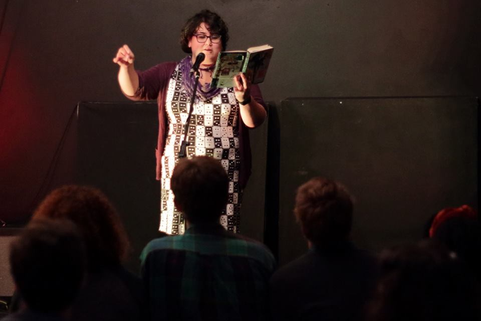 Audience-perspective picture of Cynthia on stage. She is a fat brown latinx femme, reading from her notebook and doing a gesture with her other hand on the microphone. She has short hair and is wearing a domino dress, a purple cardigan and glasses.