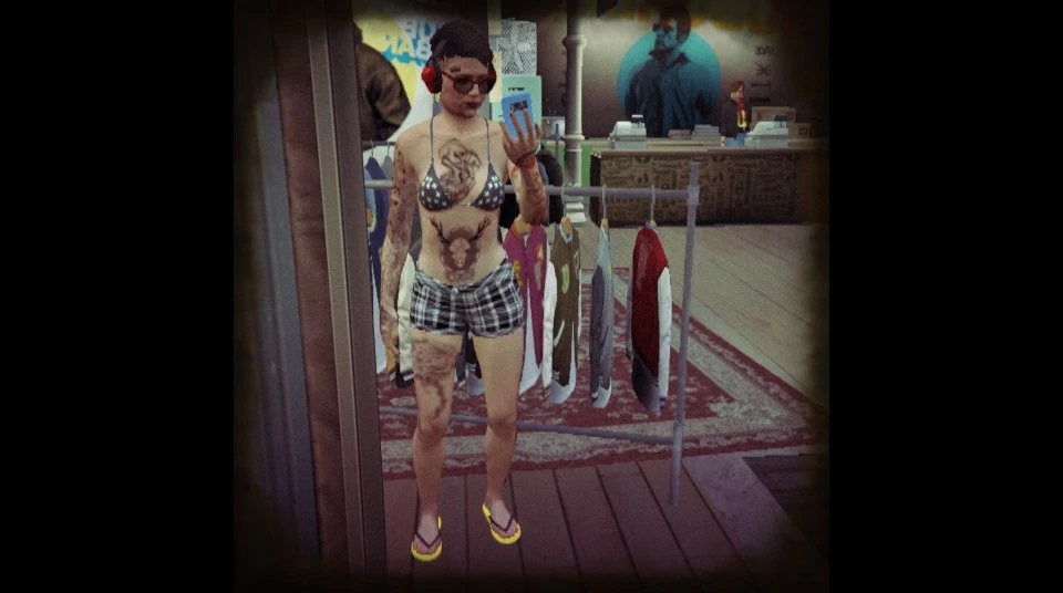 Mirror selfie of GTA Online character at a clothing shop wearing a bikini, shorts, flip flops, glasses and ear protection. She's light brown with brown hair and tattoos all over her body.