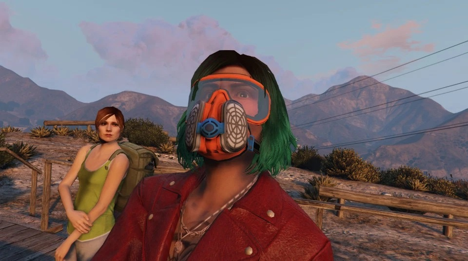 Character from GTA Online in Mount Chiliad. She has green and brown hair, wears an orange breathing mask and a red leather jacket. In the background, a backpacker looks confused.