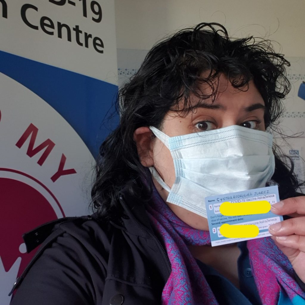 Picture of Cynthia, fat brown latinx with medium-lenght wavy brown hair, wearing a medical face mask, a black jacket, a purple and blue scarf and a blue t-shirt dress. She's joyfully looking at the camera, holding a COVID-19 vaccine card showing she is fully vaccinated now.